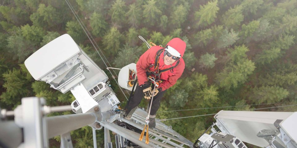 Man in red jacket climbing a cell phone tower to service it