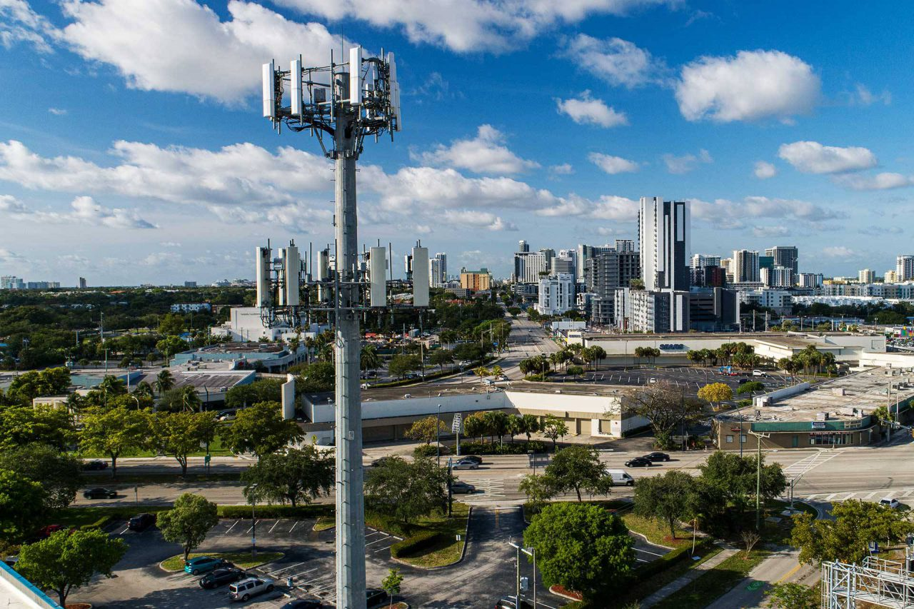 Skyline view of city with cell tower built by telecom infrastructure company Parallel Infrastructure in the foreground